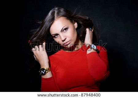 The beautiful girl with a wrist watch against a dark background - stock photo