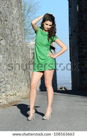 the beautiful girl with green dress walks in the ancient village of the castle - stock photo