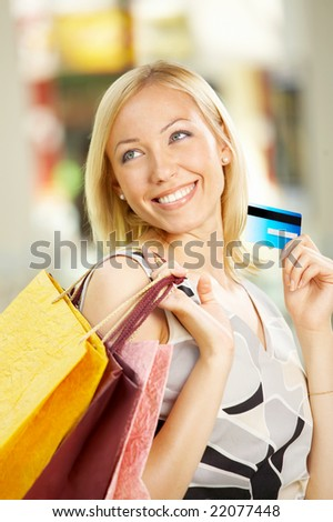 The beautiful girl with purchases and a credit card - stock photo