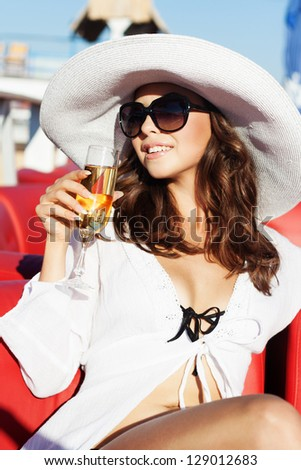 The beautiful glamour girl in a white hat on the beach - stock photo
