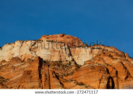 The beautiful glow of the setting sun lighting up the red and orange sandstone rock formations against a blue sky at Zion National Park, UT. - stock photo