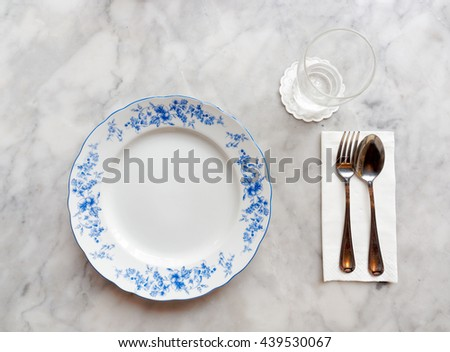 The beautiful hand painted plate in oriental styleâ??s table setting with napkin, silverware and empty glass on marble table. - stock photo