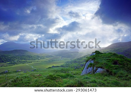 The beautiful landscape of Moll's Gap in The Ring of Kerry, Ireland, showing an early morning misty sunrise and how the clouds and shadows roll over the mountains - stock photo