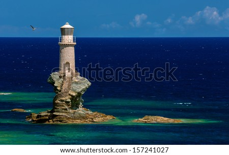The beautiful Lighthouse Tourlitis of Chora in Andros island and a seagull, Cyclades, Greece - stock photo