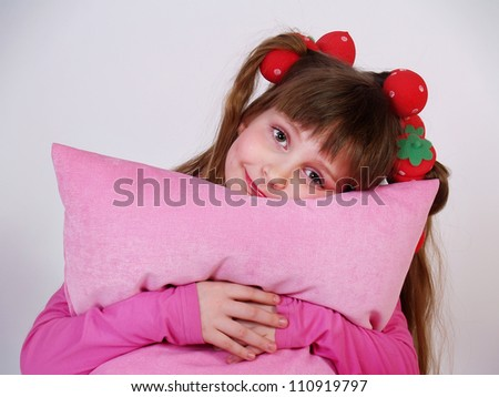 The beautiful little girl with a pink pillow in hands - stock photo