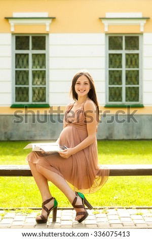 The beautiful pregnant girl in a dress sits on a bench - stock photo