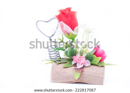 the beautiful red flower with green leaves and metal heart on log - stock photo