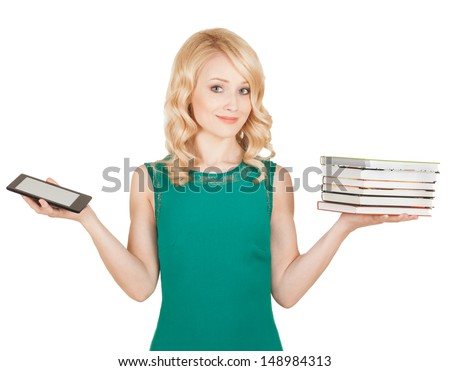 the beautiful, slender blonde compares a tablet and books - stock photo