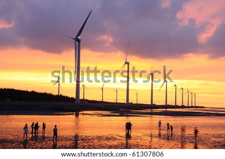 the beautiful sunset at the wind-power station - stock photo