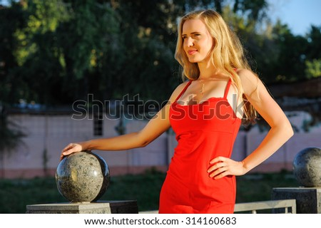 The beautiful woman in elegant red dress in the summer city - stock photo