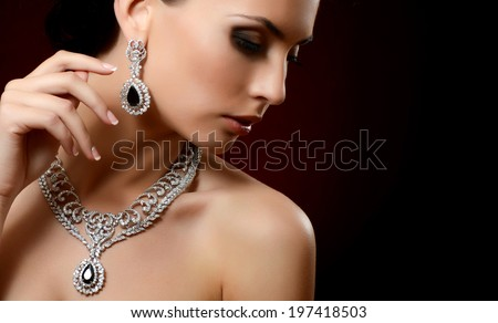 The beautiful woman in expensive pendant close-up - stock photo