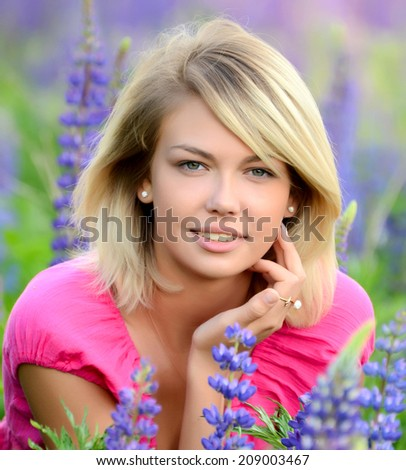 The beautiful woman in field with lupin - stock photo