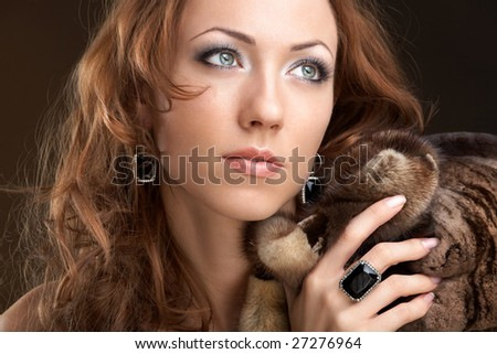 The beautiful woman in furs and jewelry - stock photo