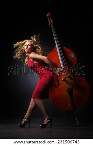 The beautiful woman is make pose with contrabass in jazz style  - stock photo
