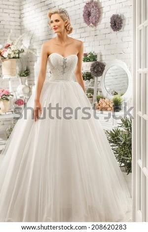 The beautiful  woman posing in a wedding dress - stock photo
