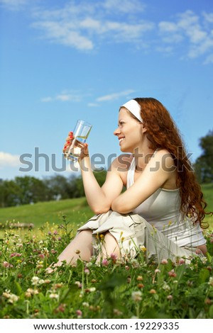 The beautiful woman sits on a lawn and drinks water - stock photo