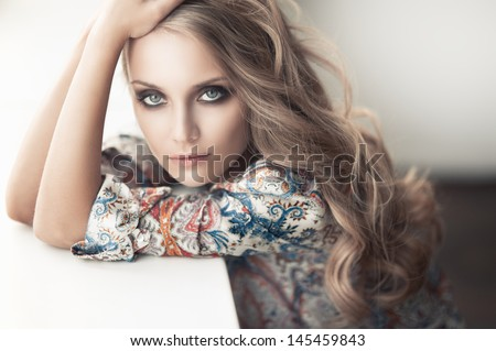 the beautiful young girl with a long fair hair looks out of the window - stock photo