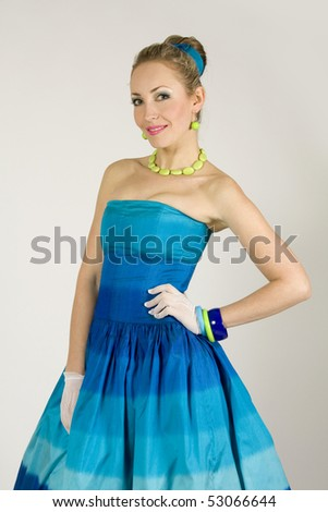 The beautiful young lady in a blue dress in retro style - stock photo