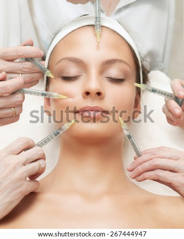 The Beautiful Young Woman Having Rejuvenating Injection against the Wrinkles - stock photo