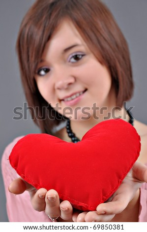 The beautiful young woman holds in hands a red heart on a grey background. Selective focus on heart. - stock photo