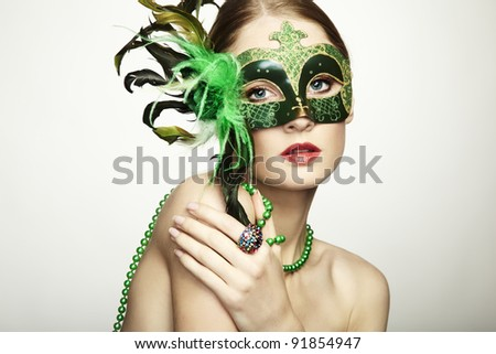 The beautiful young woman in a green mysterious venetian mask - stock photo