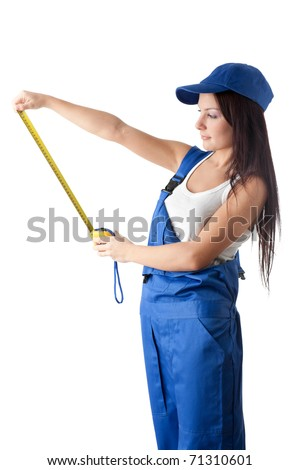 The beautiful young woman in overalls with a measuring tape in hands on a white background. - stock photo