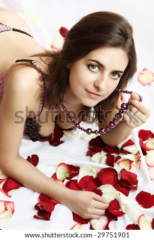 The beautiful young woman lies in petals of roses - stock photo