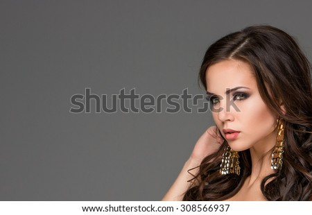 The beautiful young woman on gray background - stock photo