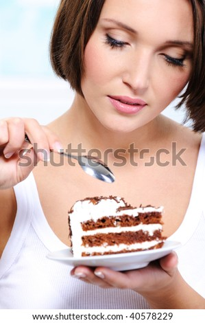 The beautiful young woman overcome by a temptation to eat a slice of a sweet cake - stock photo