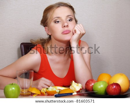 The beautiful young woman sits at a table and eats fruit - stock photo