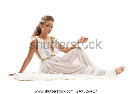 The Beautiful Young Woman Sitting on the Floor, Holding the Gold Bowl with Nectar and Wearing White and Gold Greek Costume on the White Background - stock photo