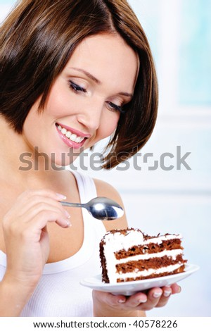 The beautiful young woman with a spoon in hands is going to eat a sweet pie - stock photo