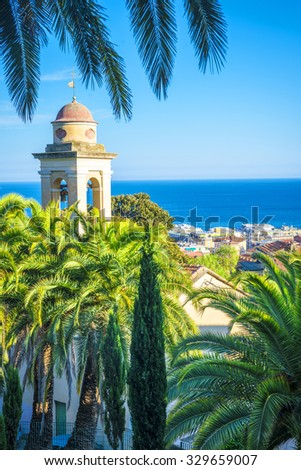 the belfry and church's roof is hiding behind the palms, sanremo, italy - stock photo