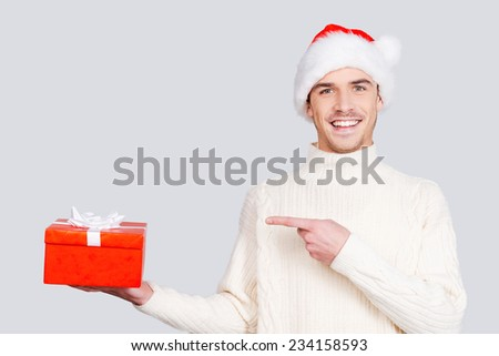 The best Christmas present. Cheerful young man in Santa hat holding a gift box and pointing it while standing against grey background - stock photo