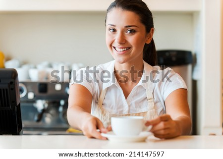 The best coffee in town for you. Beautiful young woman in apron serving coffee and smiling while standing in coffee shop - stock photo