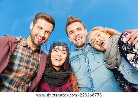 The best friends ever. Low angle view of four young happy people bonding to each other and smiling with blue sky as background - stock photo