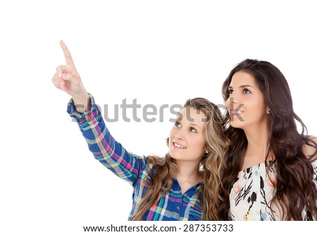 The best friends. Two pretty women indicating something with the finger isolated on a white background - stock photo
