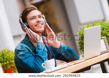 The best start of my day! Cheerful young man holding hands on headphones while sitting at sidewalk cafe - stock photo