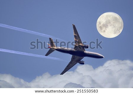 The big airplane flying across a full moon - stock photo