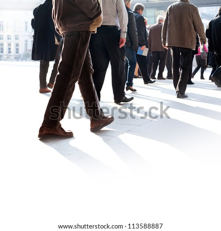 The big group of older persons. People walking against a light background. - stock photo