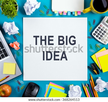 The big idea. Text words advice on office table desk with supplies, white blank note pad, cup, pen, pc, crumpled paper, flower, wooden background. Top view - stock photo