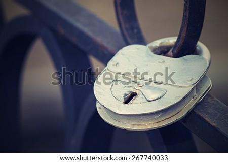 the big old iron padlock of silvery color is locked on the forged fencing, the image of the digital photo with a retro effect, - stock photo
