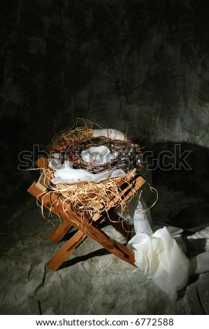 The birth and death of Christ represented by manger and crown of thorns. - stock photo