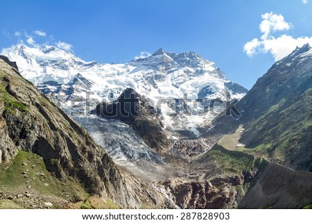 The birth of the glacial river in the rays of the summer sun among the snowbound Himalayan peaks and a melting glacier in the Zanskar valley, northern India - stock photo