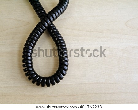 The black a twisted wire(handset) twist look like infinity sign on wooden office table, close-up.  - stock photo