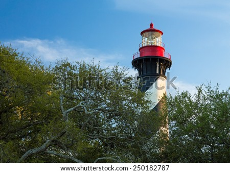 The black and white spiral striped lighthouse at St. Augustine, Florida is topped with a bright red lantern room. - stock photo