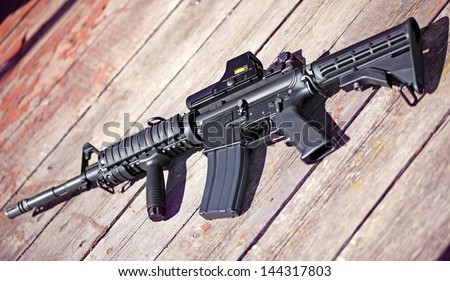 The Black Rifle. AR-15 assault carbine (M4A1) on a wooden surface. Shallow DOF. - stock photo
