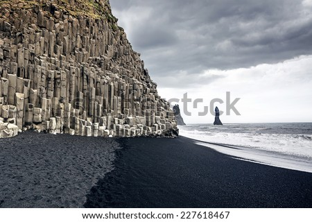 The black sand beach of Reynisfjara and the mount Reynisfjall from the Dyrholaey promontory in the southern coast of Iceland. - stock photo