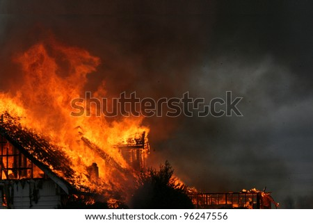 The blaze and smoke from a nighttime house fire creates an eerie dramatic photograph that could be an equally dramatic background. - stock photo