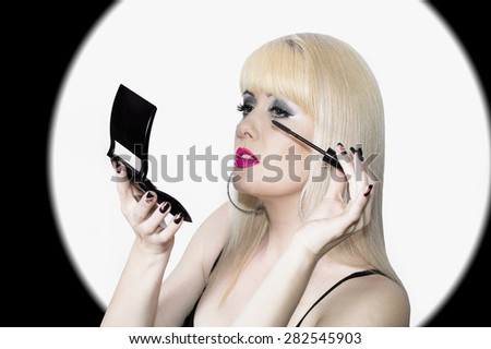 The blonde makes up eyelashes, a make-up and style - stock photo